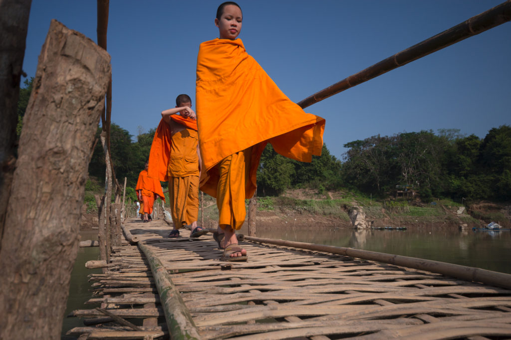 Novices traversant un pont de bois au-dessus du Mékog à Luang Prabang, Laos