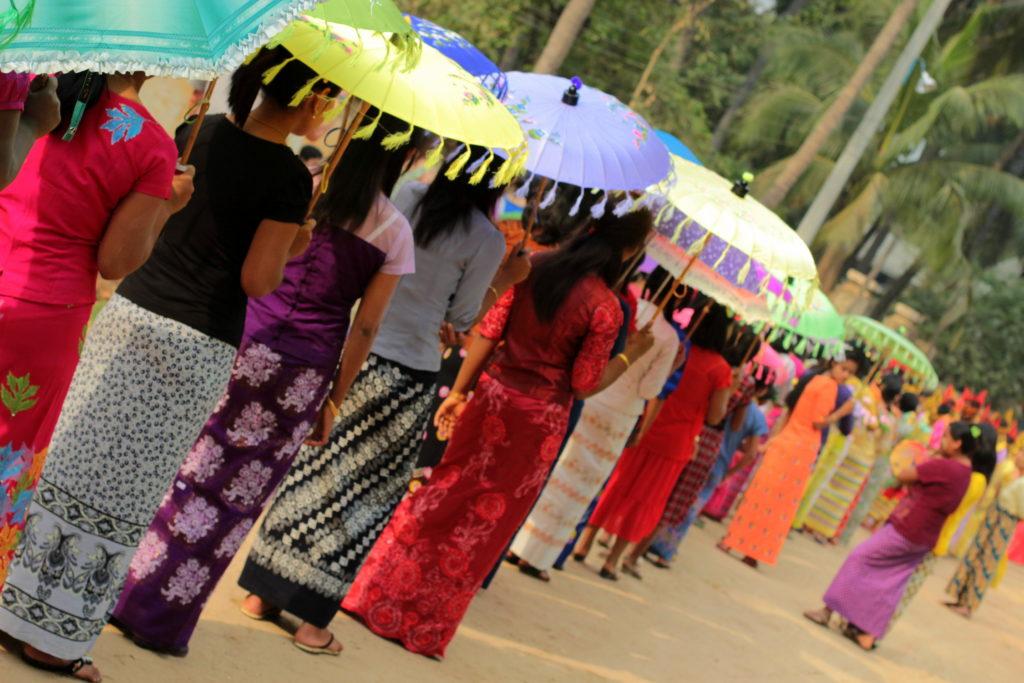Femmes en longyi et ombrelles à la cérémonie de Shinbyu, Bagan, Birmanie
