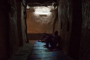 Hommes priant dans l'intérieur sombre de la Grande Mosquée de Bobo Dioulasso, Burkina Faso