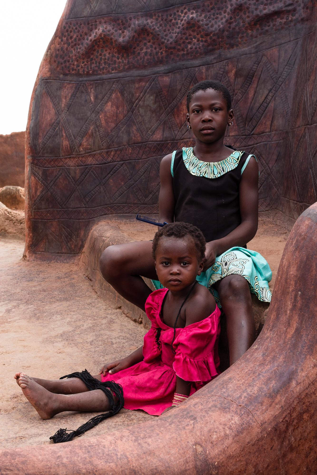 Filles se coiffant devant les cases du village de Tangassogo, Burkina Faso