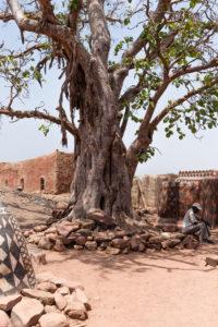 Homme assis sur un tas de pierres disposées à l'ombre d'un arbre à l'entrée de la cour royale de Tiébélé, Burkina Faso