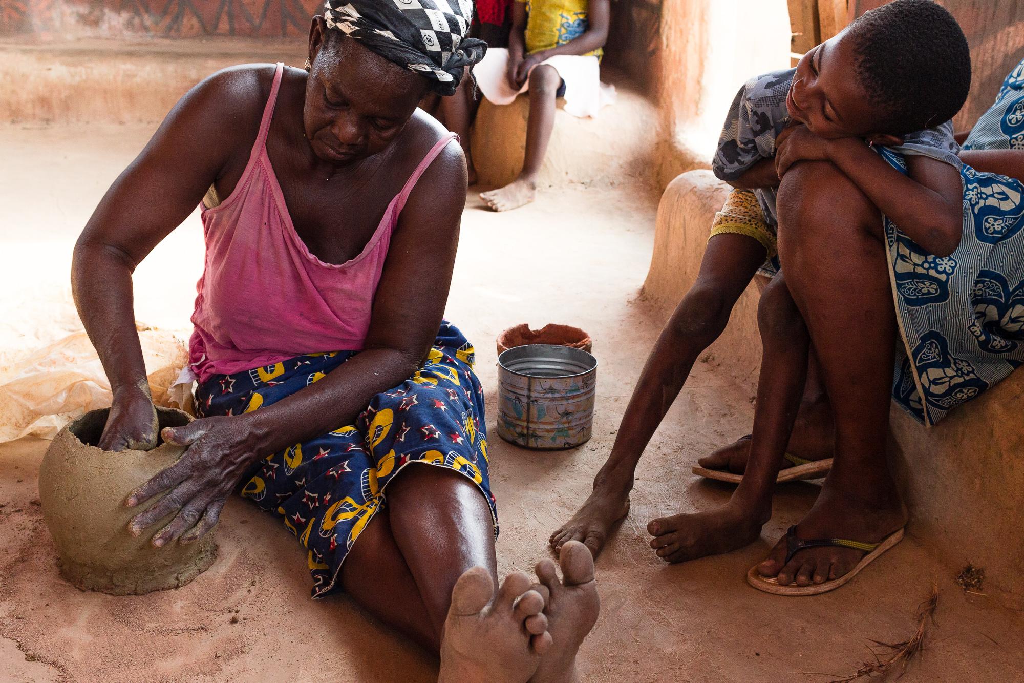 Femme modelant un pot de terre dans la région de Tiébélé, Burkina Faso, sous le regard d'un enfant