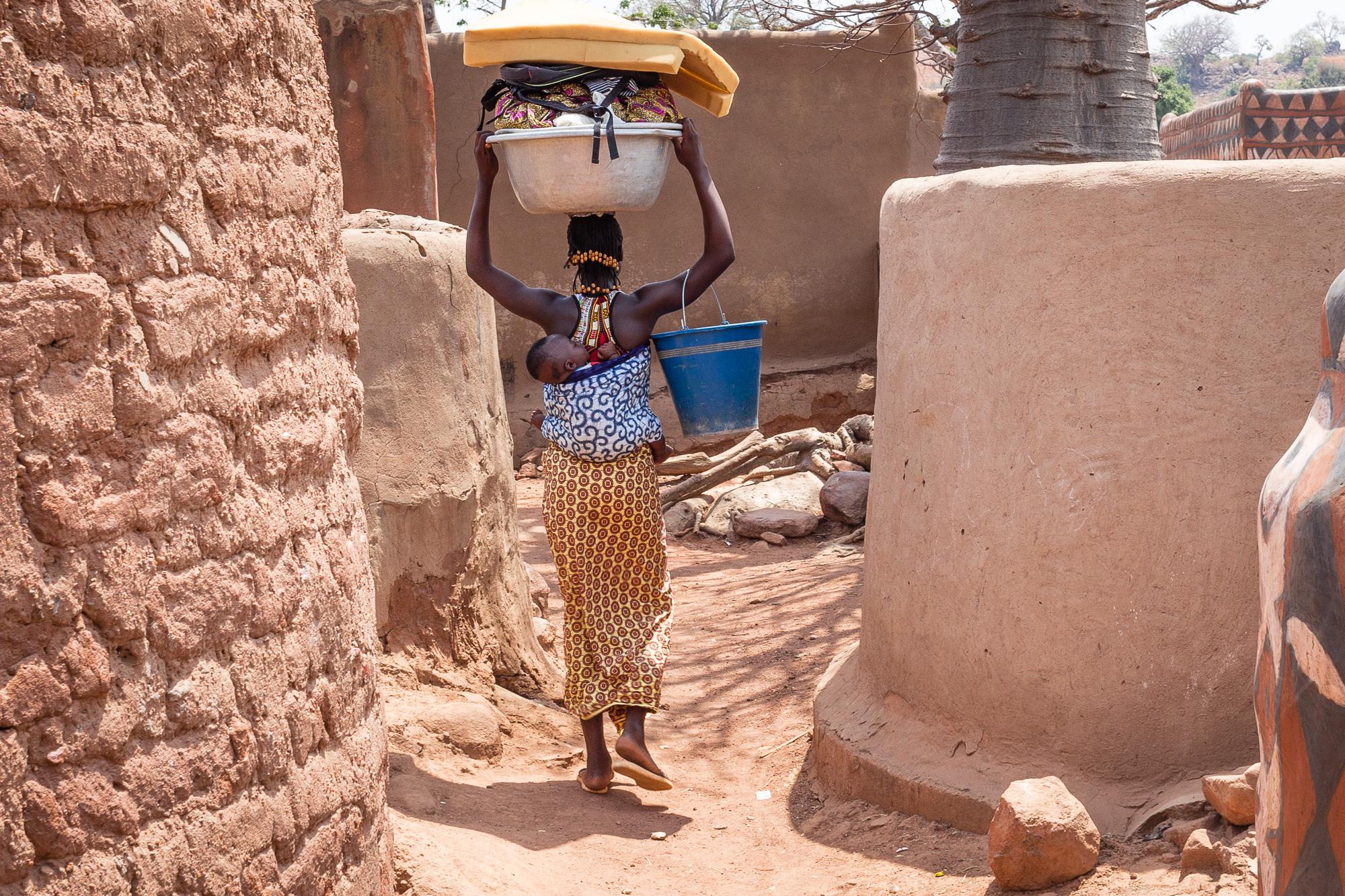 Femme avec enfant dans le dos et bassine remplie de linge sur la tête, dans les ruelles de Tiébélé, Burkina Faso