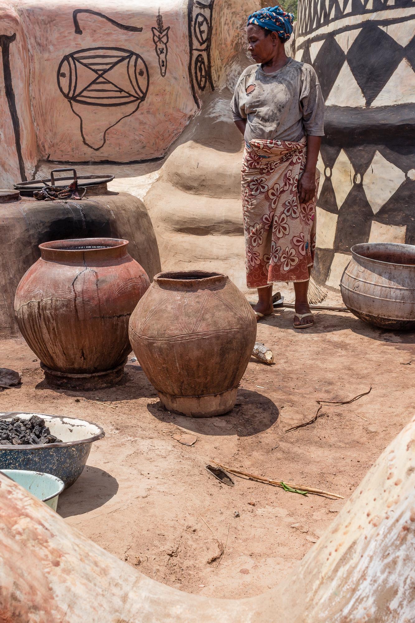 Femme se tenant devant sa brasserie de dolo, cour royale, Tiébélé, Burkina Faso
