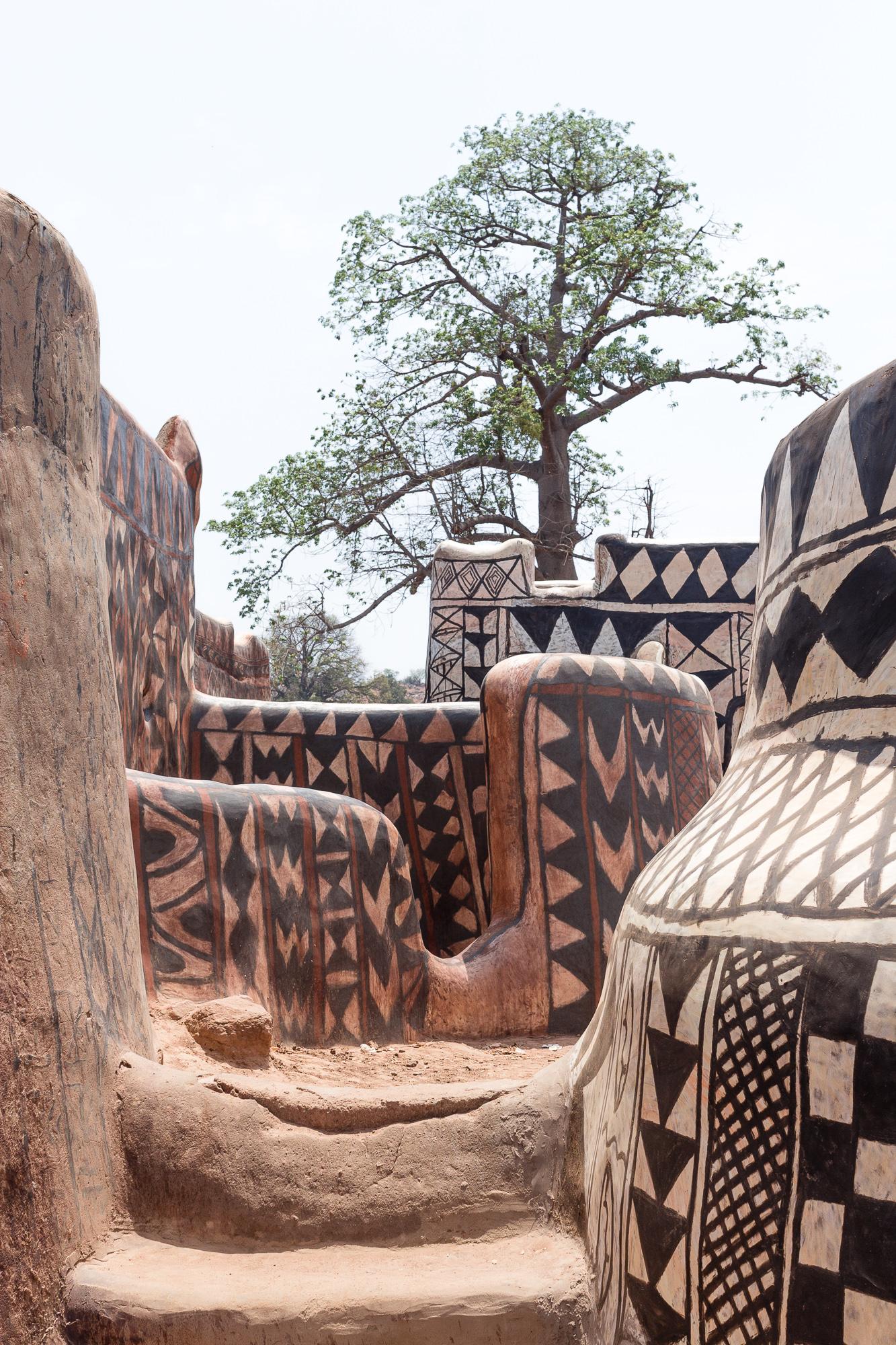 Cases décorées de la cour royale de Tiébélé et arbre au loin, Burkina Faso