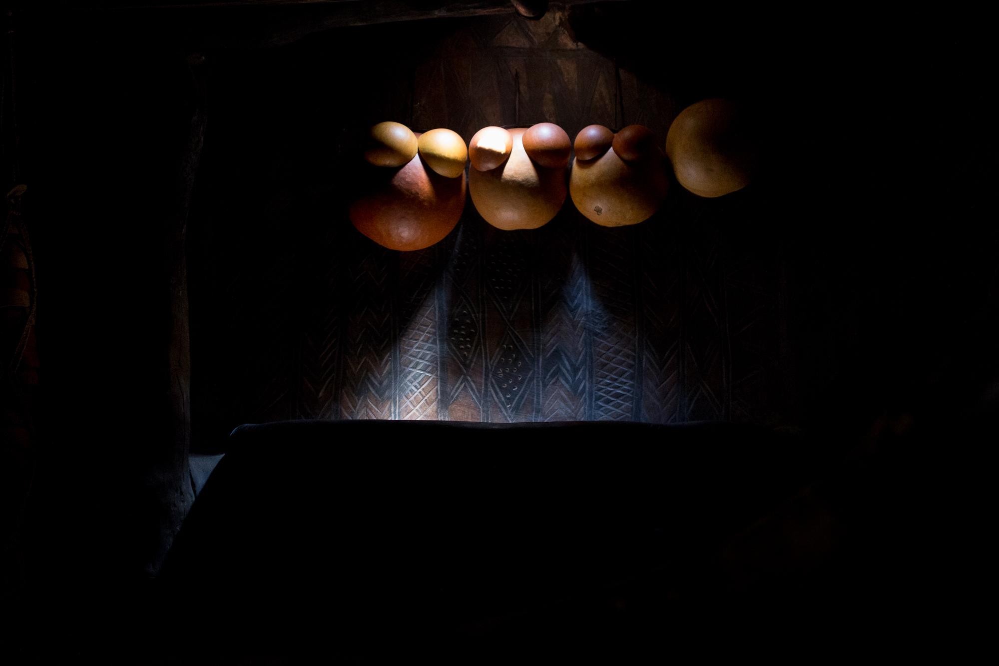 Calebasses suspendues dans l'obscurité d'une case du village de Tiébélé, Burkina faso