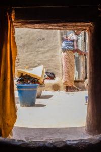 Femme avec enfant dans le dos fermant la porte de sa case, Tiébélé, Burkkina Faso
