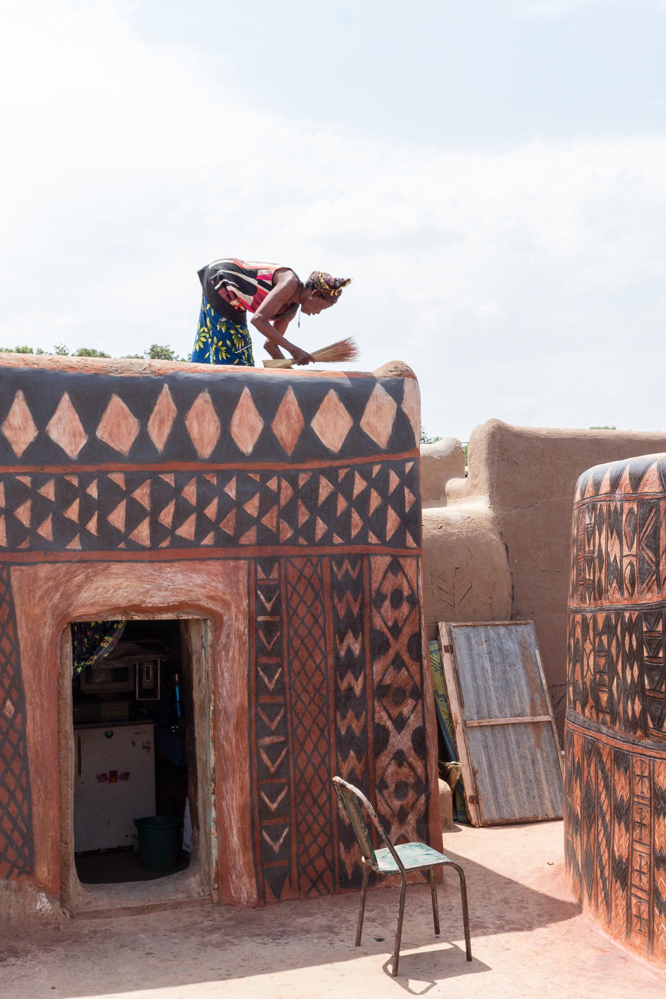 Femme se préparant à passer une couche de vernis sur les motifs peints de sa case, cour royale, Tiébélé, Burkina Faso