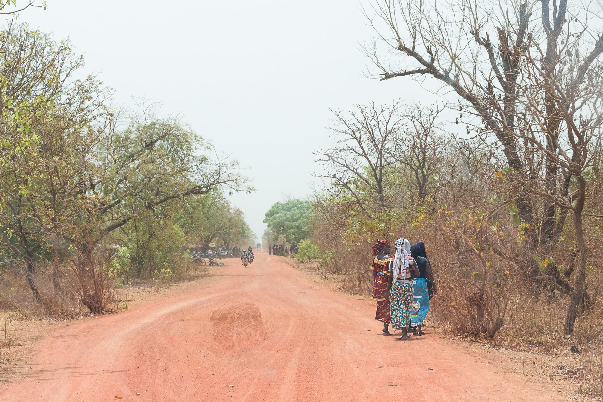 Femmes vêtues de wax sur le bord de la piste rouge entre Nazinga et Bobo Dioulasso, Burkina Faso
