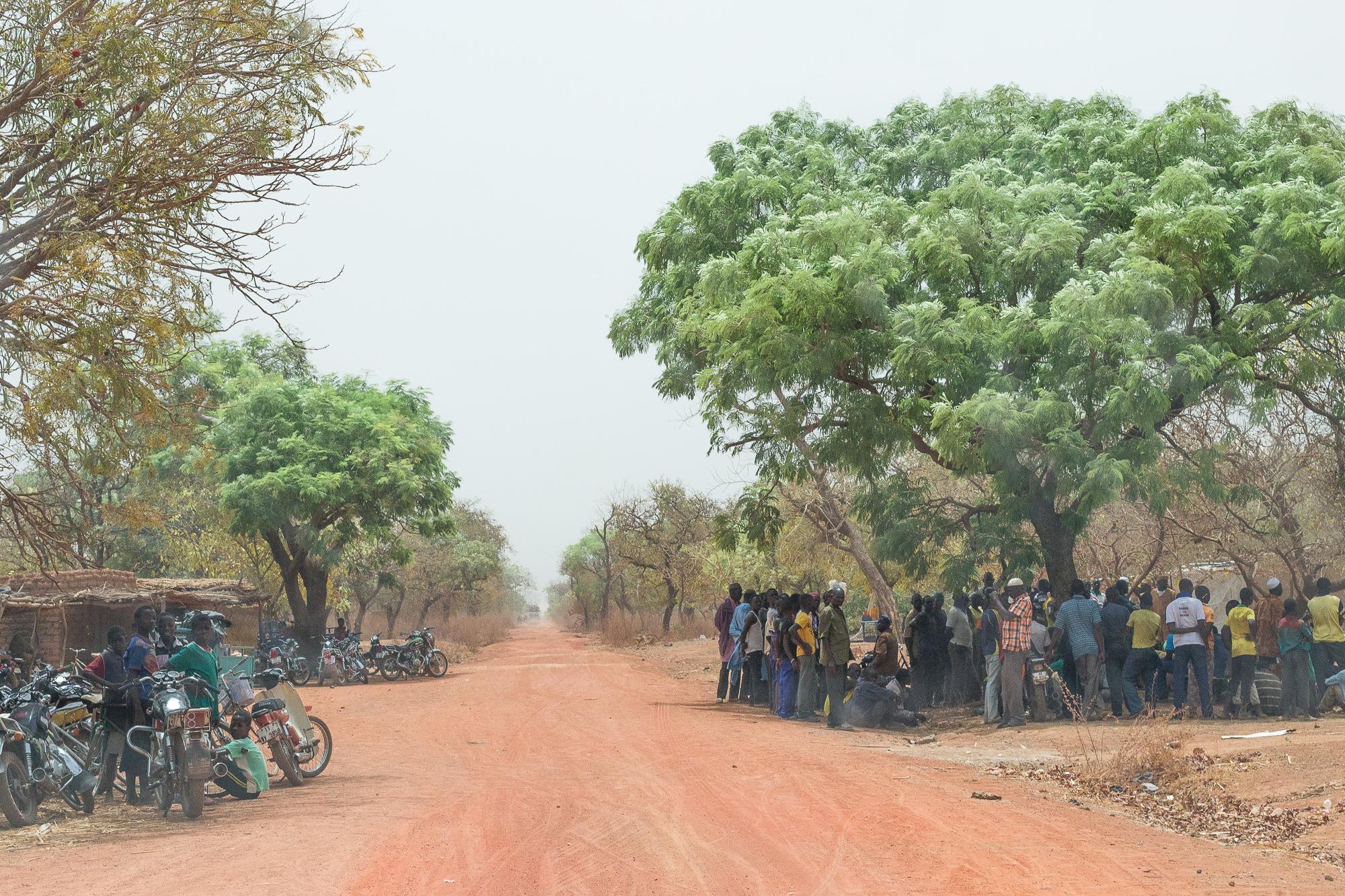 Attroupement d'hommes sous un arbre au bord de la piste entre Nazinga et Bobo Dioulasso, Burkina Faso