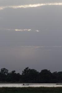Pêcheur en pirogue sur le lac de Tengrela après le coucher du soleil, région de Banfora, Burkina Faso