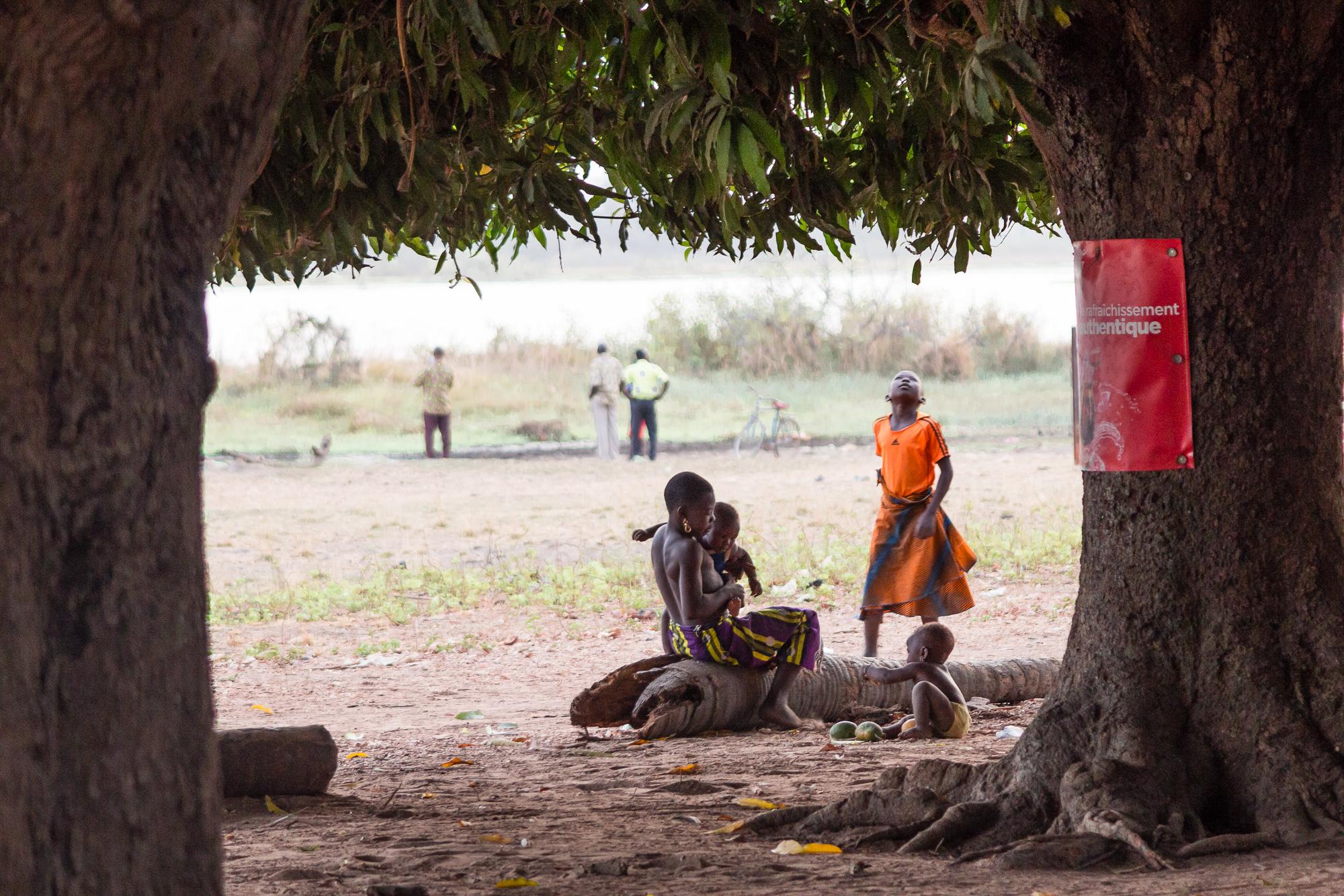 Famille Burkinabé sous un manguier sur les rives du lac de Tengrela, région de Banfora, Burkina Faso