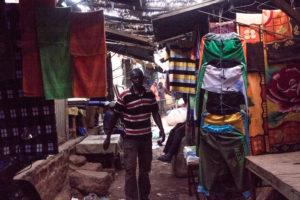 Intérieur sombre et stands de vêtements du marché de Gaoua, Burkina Faso