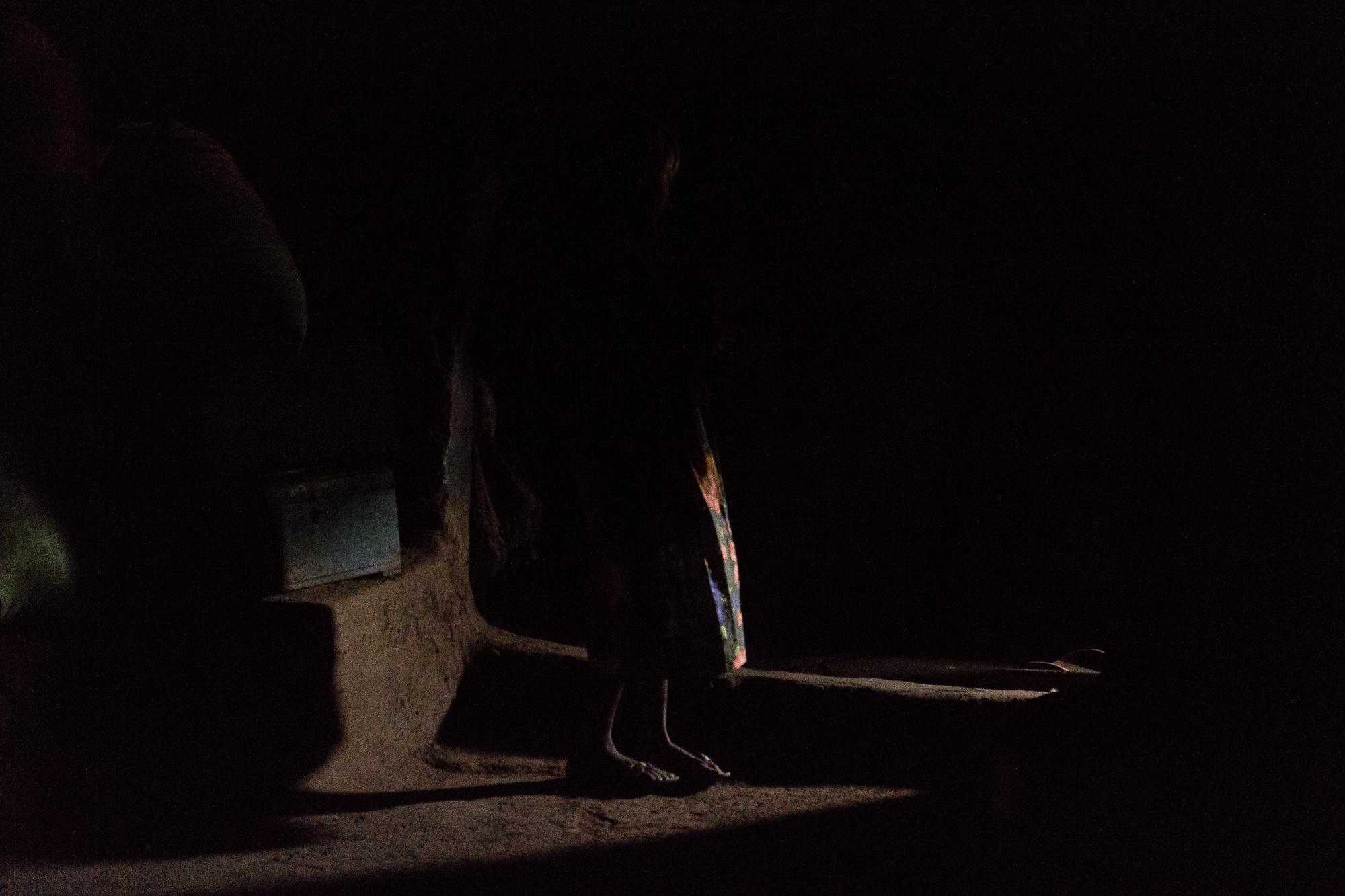 Silhouette dans la pénombre d'une case du village Lobi de Sansana, Burkina Faso