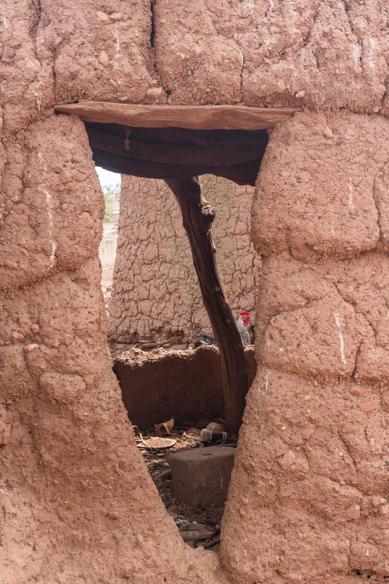 Ouverture sur l'intérieur d'une case et petite poule dans le fond, village Lobi de Sansana, Burkina Faso