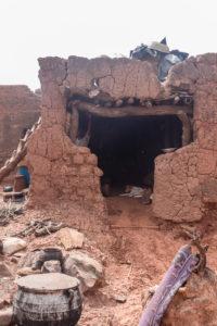 Cas vétuste abritant un chien et une jeune femme avec cuisine extérieure dans le village Lobi de Sansana, Burkina Faso