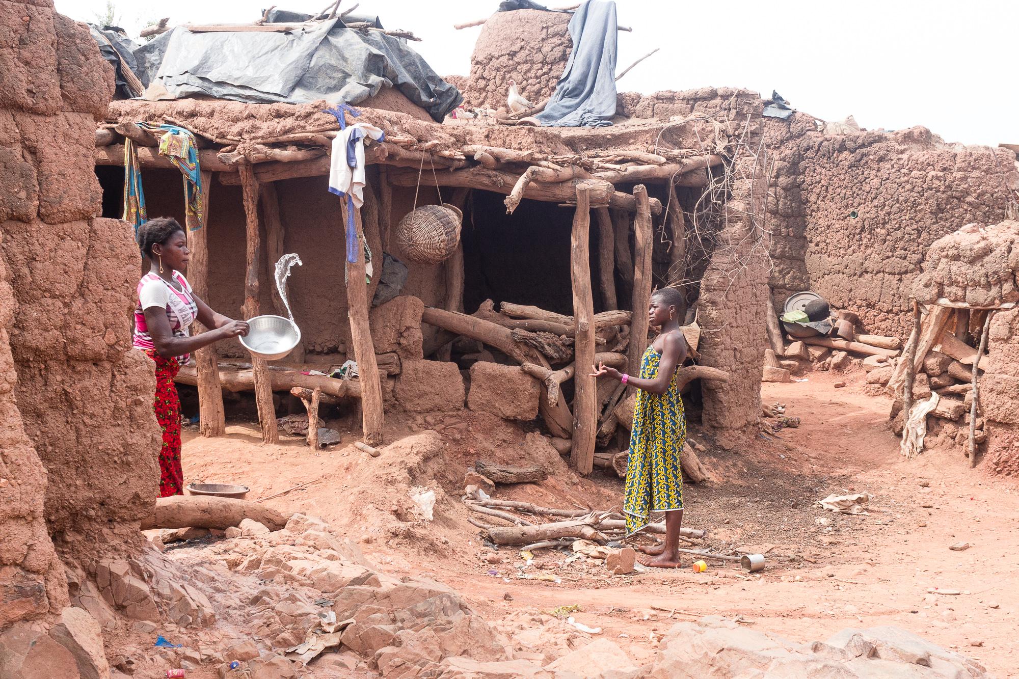 Femmes jetant l'eau d'une bassine dans les rues du villages Lobi de Sansana, Burkina Faso