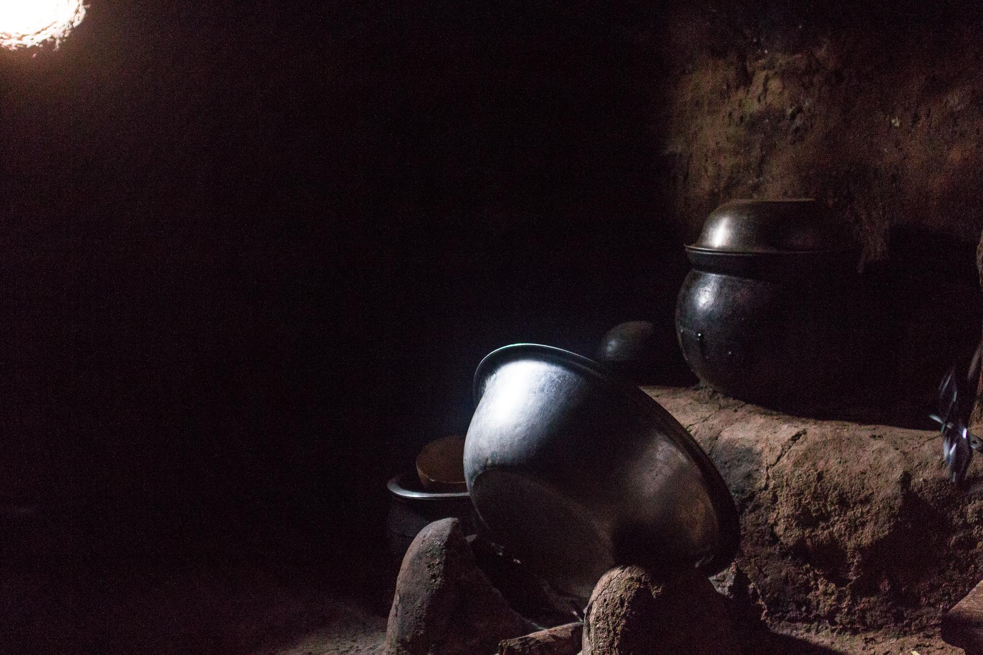 Ustensiles de cuisine dans la pénombre d'une case éclairés par un rai de lumière, village Lobi de Sansana, Burkina Faso