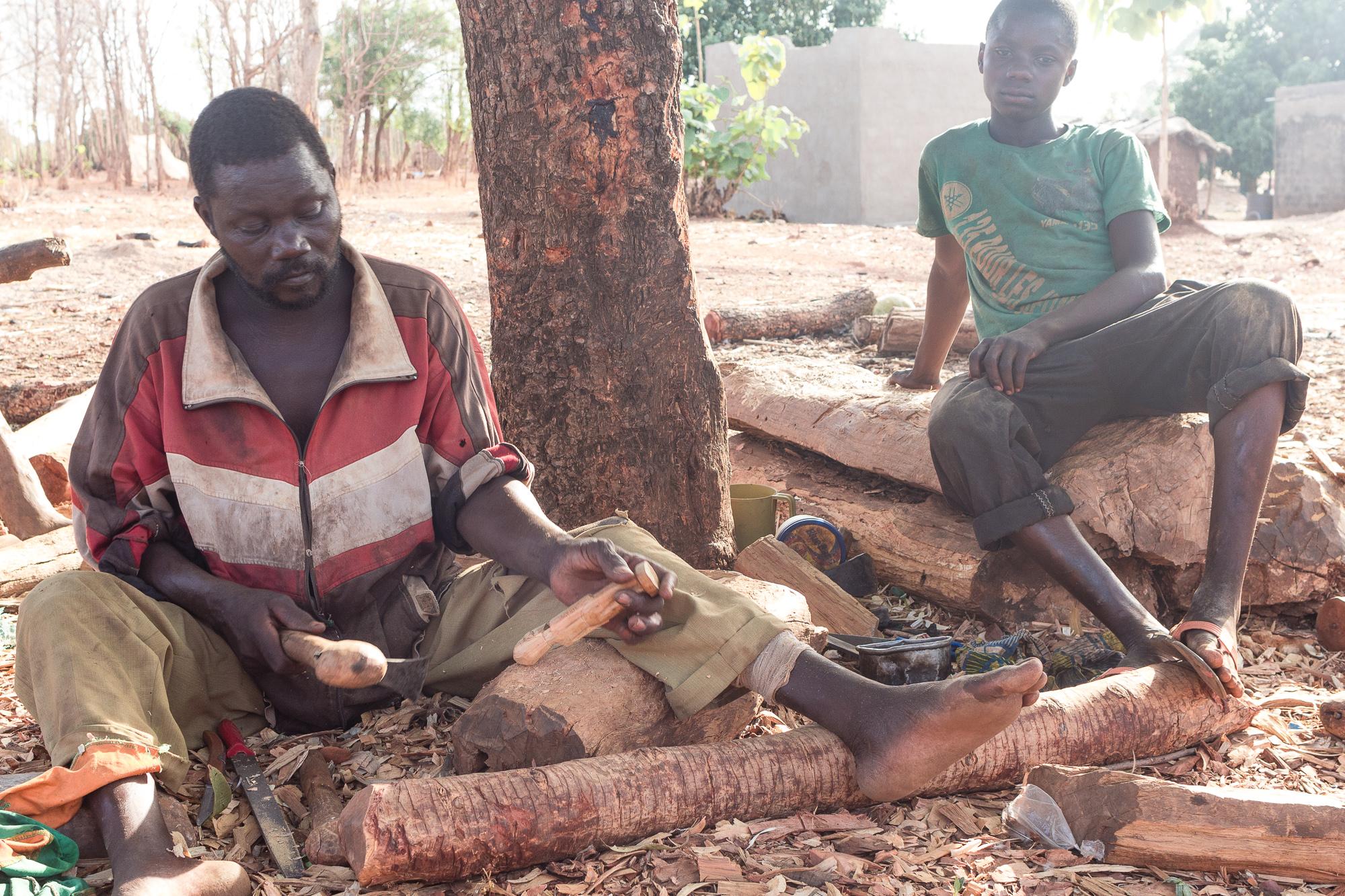 Sculpteur sur bois en train de façonner une figurine avec un maillet, village d'artisans Lobi, Burkina Faso