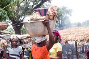 Femme portant une bassine remplie sur sa tête, marché de Doudou, pays Lobi, Burkina Faso