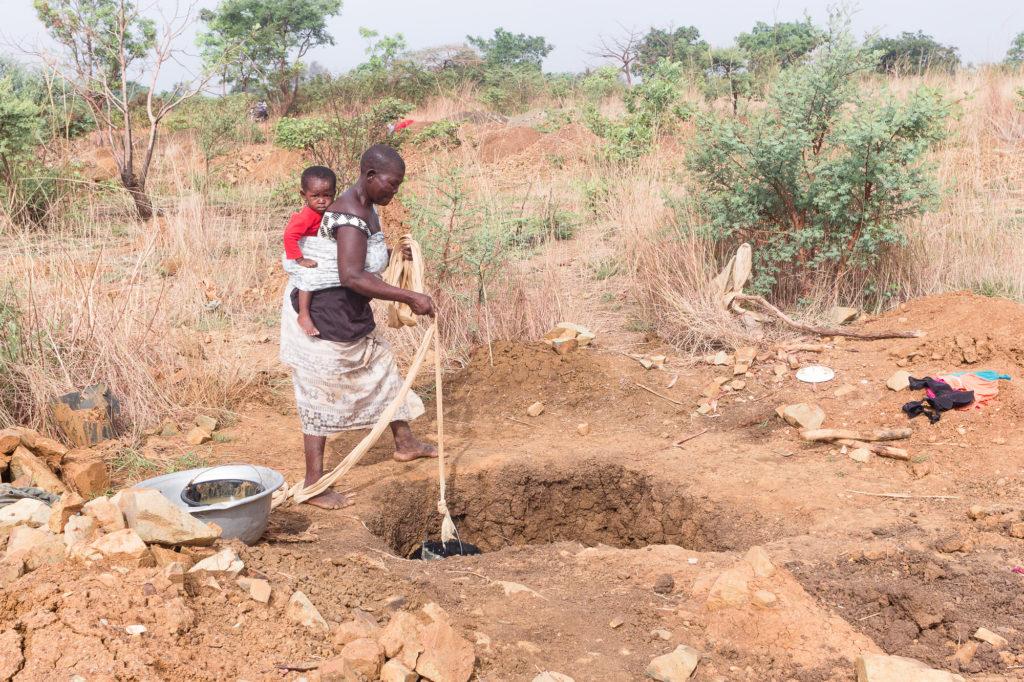 Chercheuse d'or avec enfant sur le dos descendant un seau dans un puits, pays Lobi, Burkina Faso