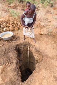 Vue plongeante sur chercheuse d'or avec enfant sur le dos descendant un seau dans un puits, pays Lobi, Burkina Faso