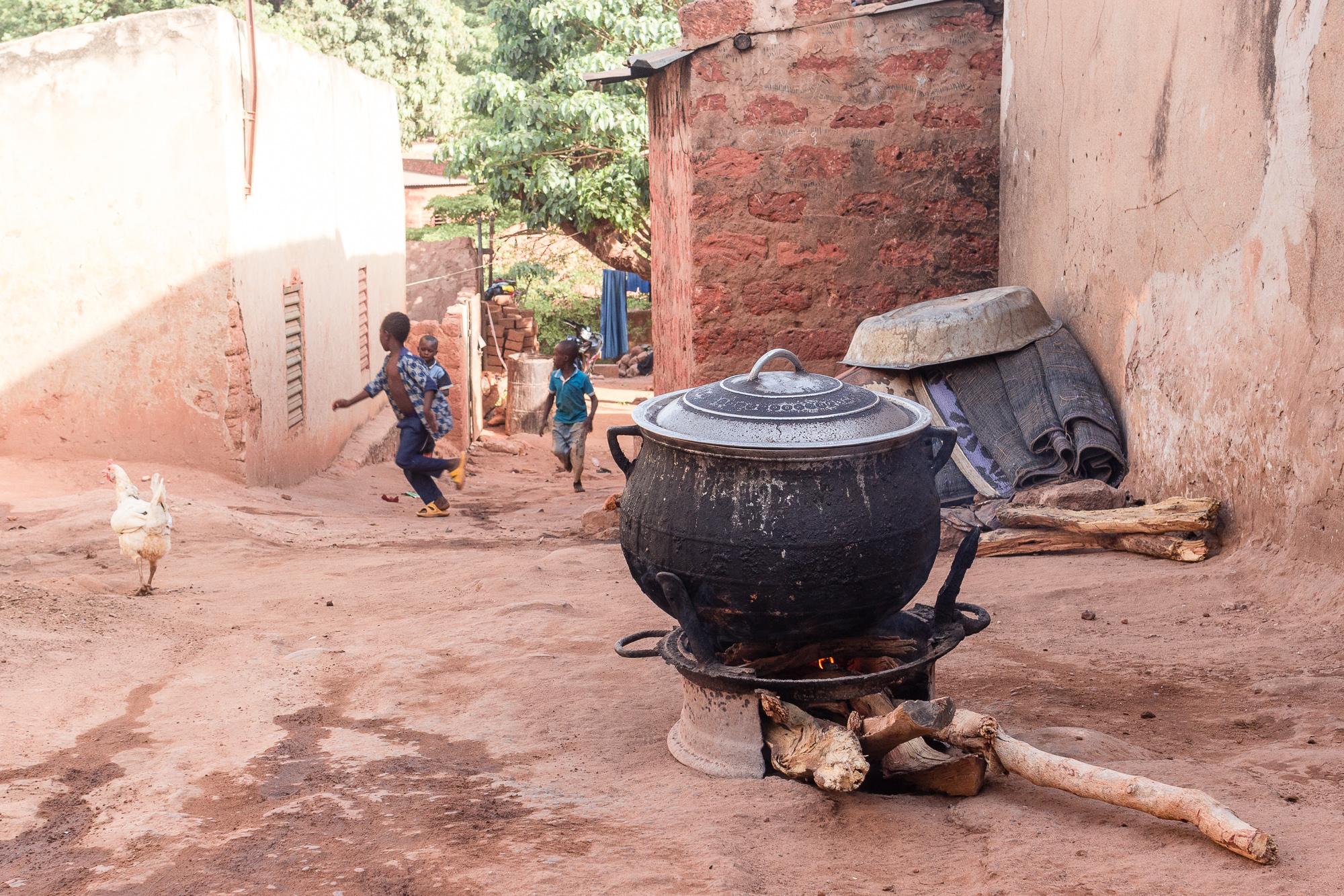 Marmite sur feu de bois, poule et enfants courant au loin dans les ruelles du Vieux Bobo, Bobo Dioulasso, Burkina Faso