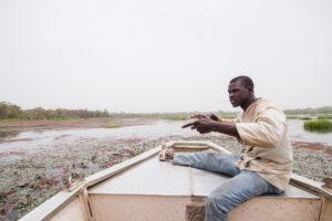 Homme en pleine discussion assis à l'avant d'une barque sur la mare de Bala, Burkina Faso