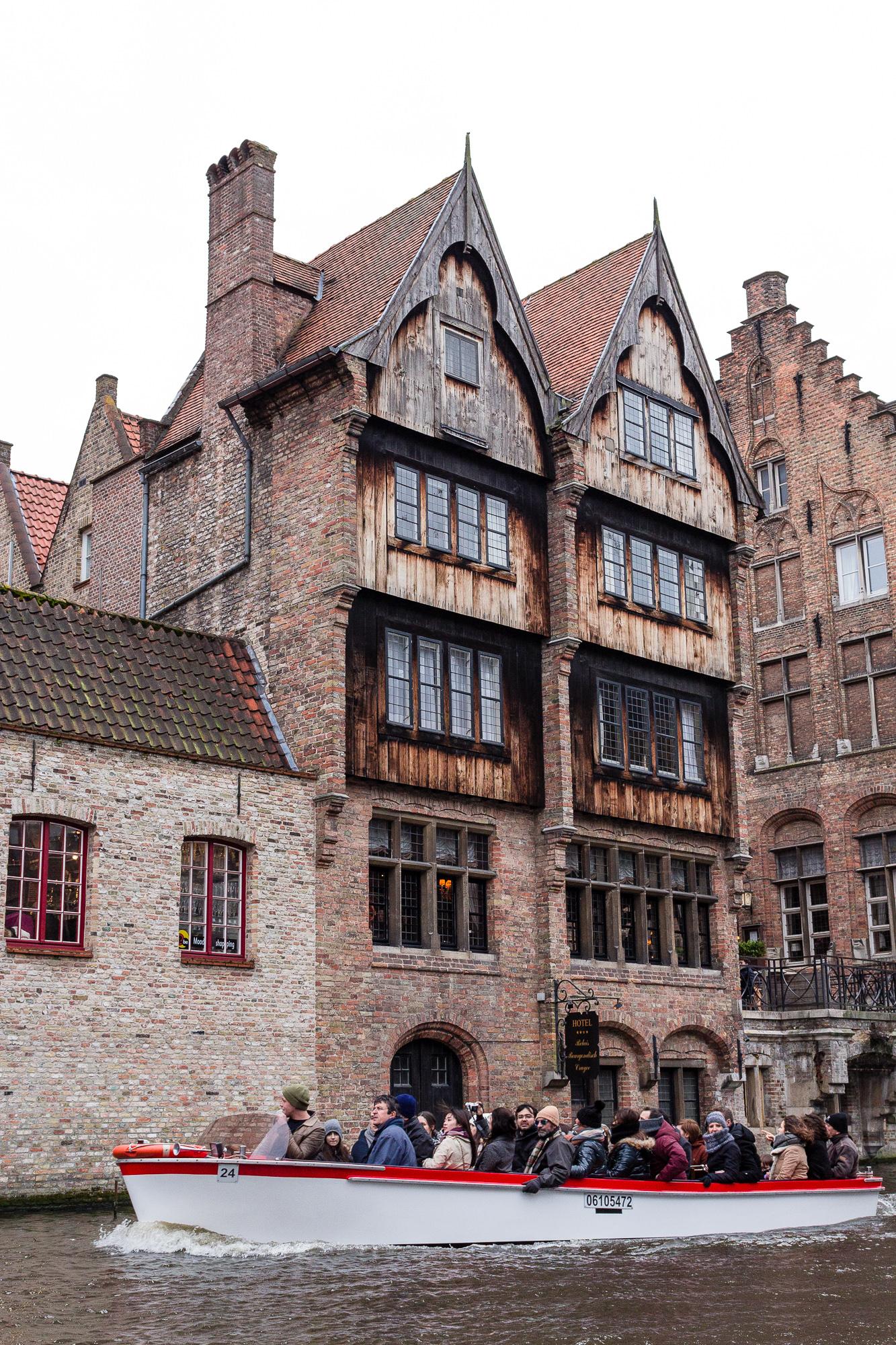 Touristes en barque sur les canaux de Bruges, et maison médiéval en arrière plan, Belgique
