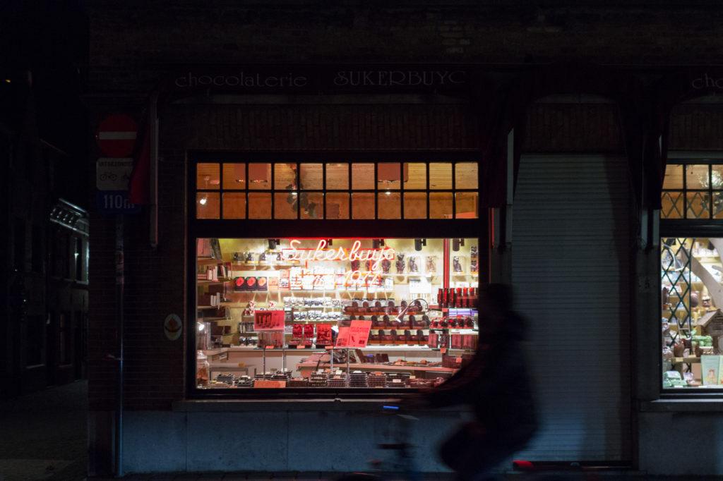 Boutique de confiseries éclairée dans la nuit, Bruges, Belgique