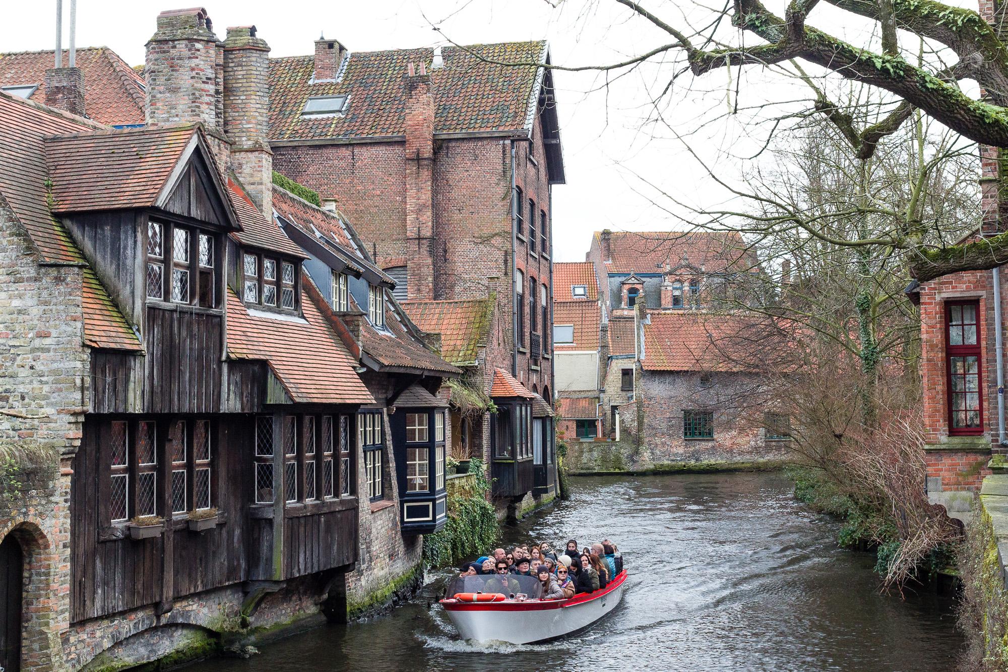 Touristes en barque sur les canaux de Bruges bordés de maisons médiévales, Belgique