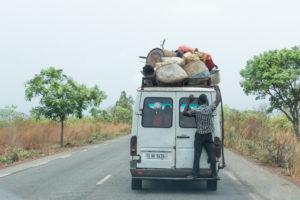 Un homme accroché à l'arrière d'un taxi-brousse très chargé, sur la route, Burkina Faso
