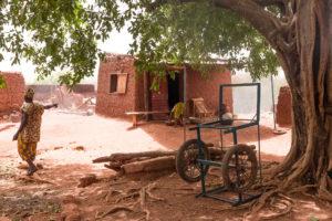 Habitant de Koumi désignant une case de banco au pied d'un ficus, village traditionnel Bobo de Koumi, Burkina Faso