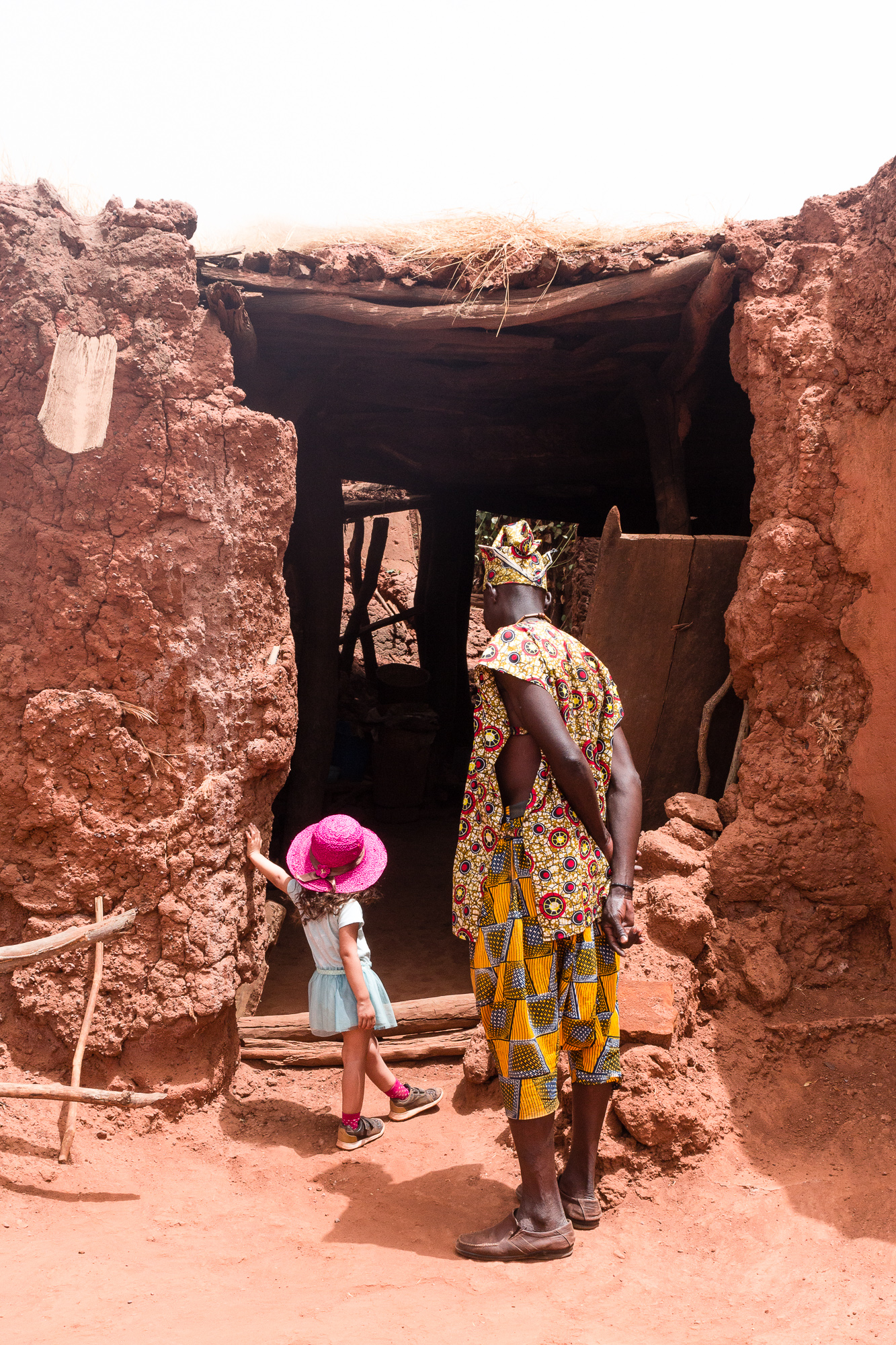 Fillette et habitant de Koumi regardant l'entrée d'une case, village traditionnel Bobo de Koumi, Burkina Faso