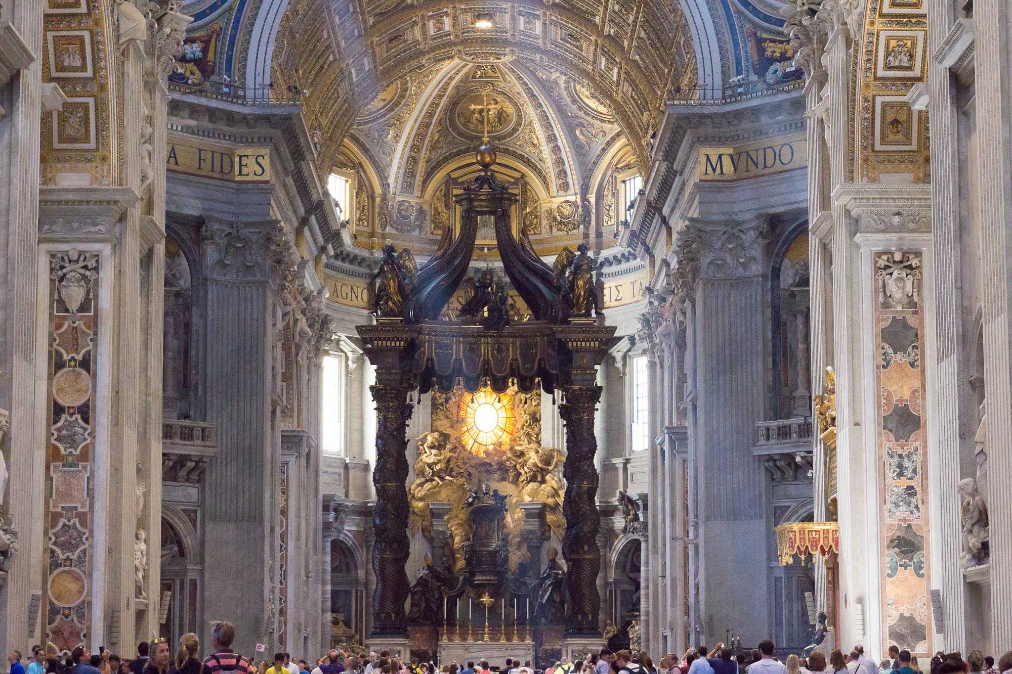Sous la coupole de la Basilique Saint Pierre, nimbée de lumière, le baldaquin du Bernin et la foule de touristes, Vatican