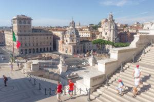 Vue sur la Piazza Venezia depuis les escaliers du monument à Victor-Emmanuel II, et famille de touristes aux couleurs de l'Italie, Rome