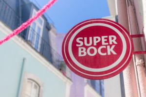 Panneau Super Bock, guirlande et façades pastels, Alfama, Lisbonne, Portugal