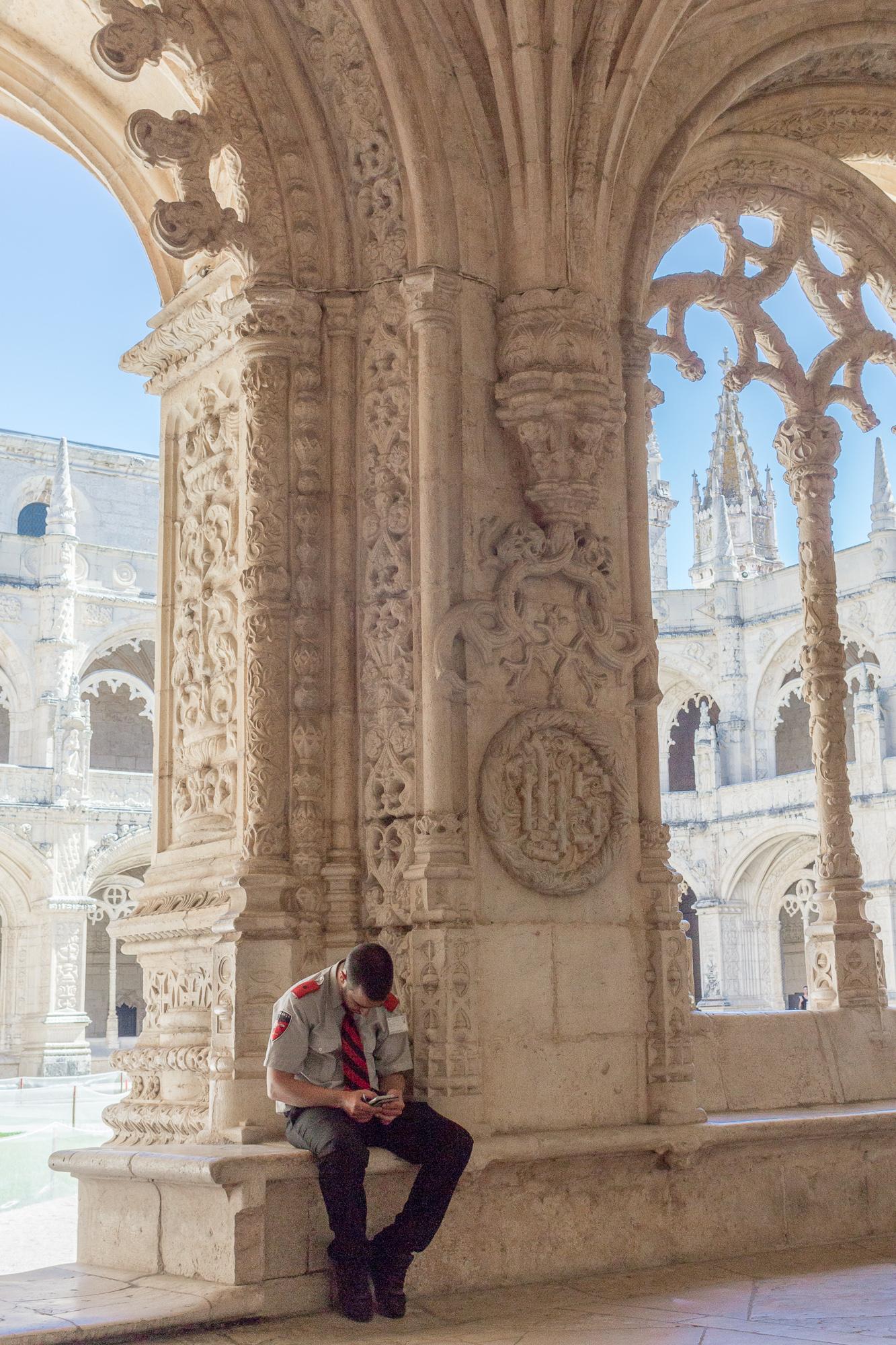Un gardien du monastère des Hiéronymites assis à l'ombre du cloître, les yeux sur son téléphone, Belém, Lisbonne, Portugal