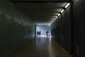 Musicien et passantes au fond d'un tunnel, rai de lumière, Lisbonne, Portugal