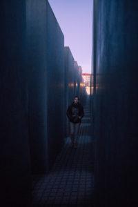 Un passant entre les stèles du mémorial juif à Berlin