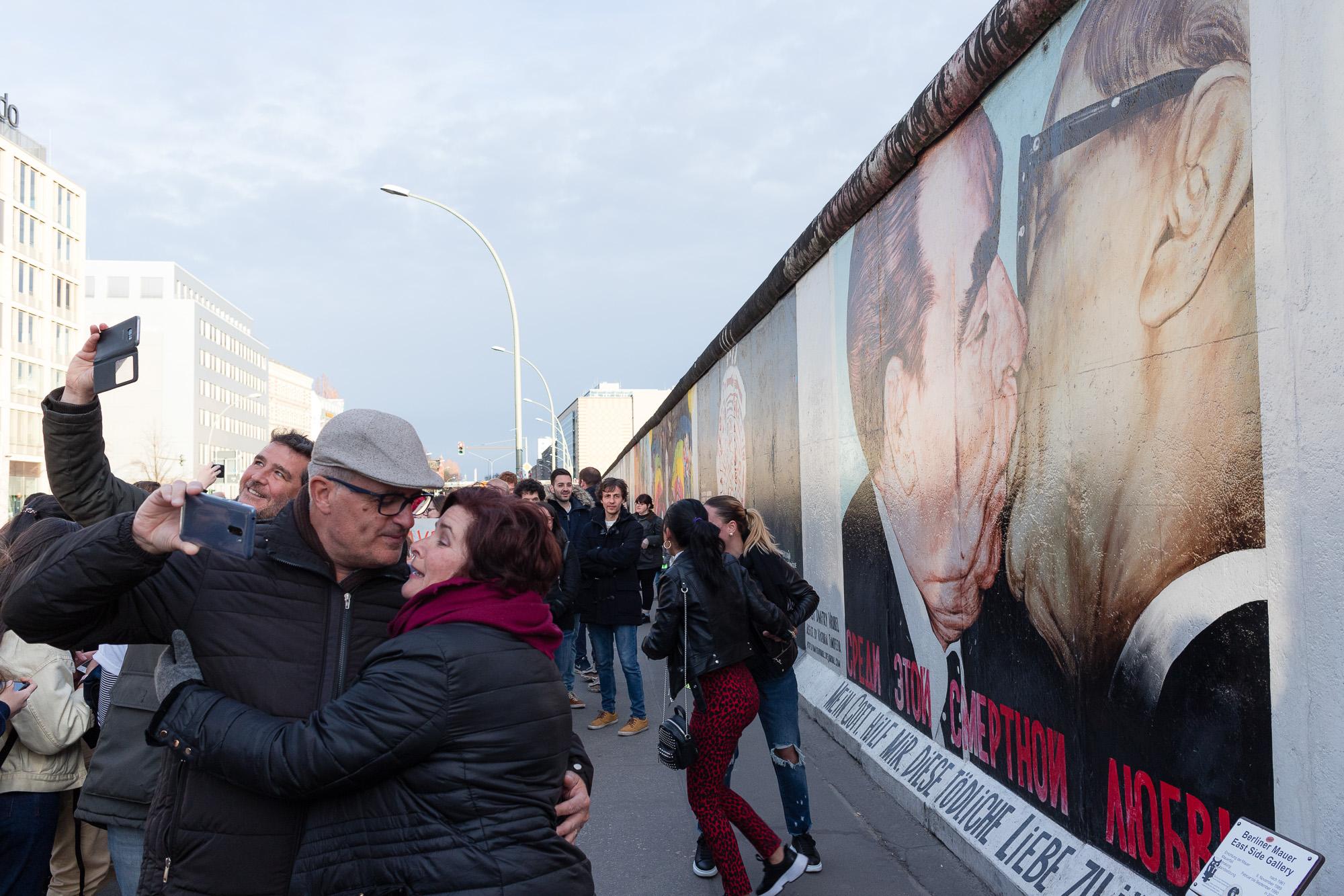 Touristes s'embrassant devant la fresque le baiser de l'amitié