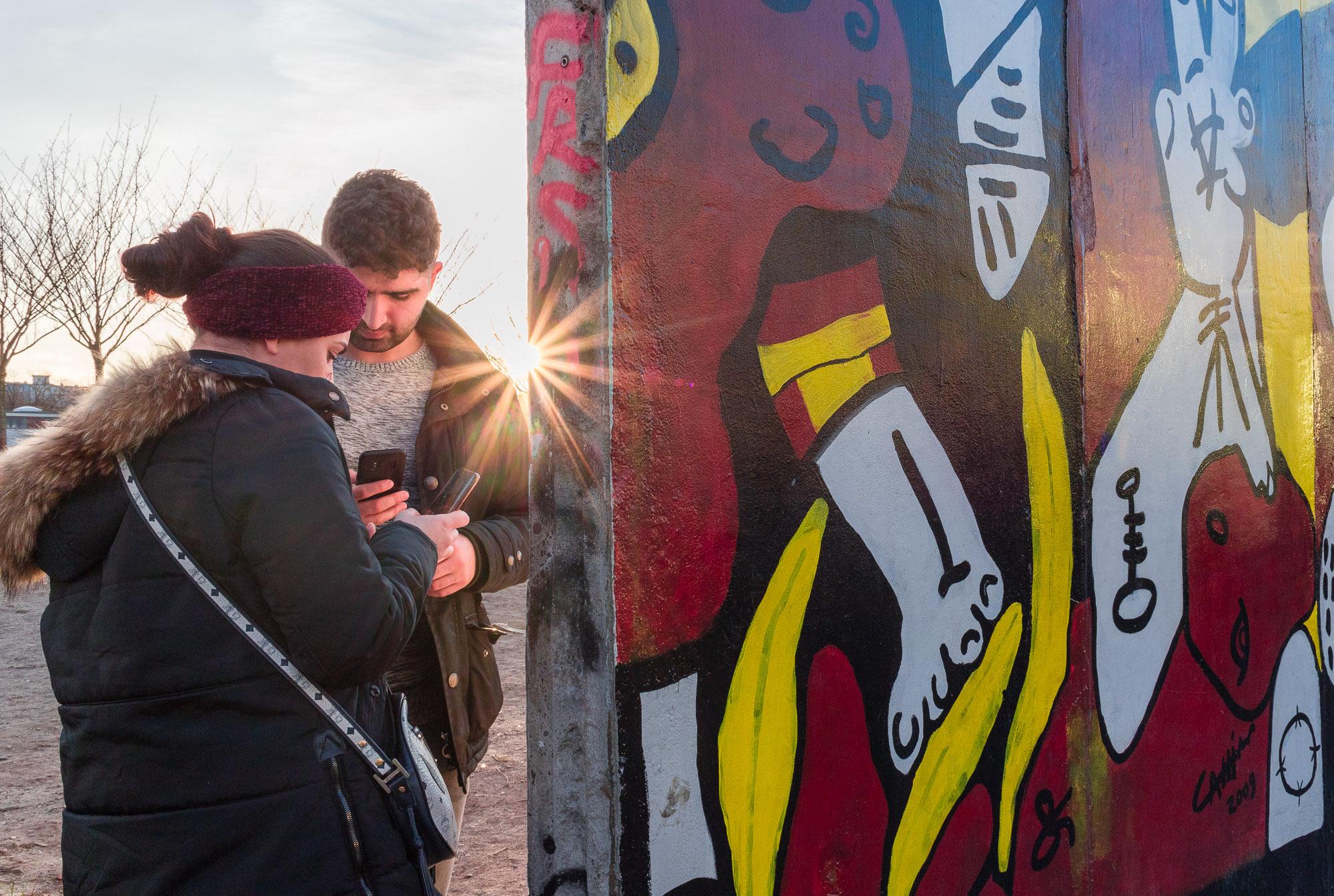 Touristes utilisant un téléphone devant une fresque du mur de Berlin et rayon de soleil