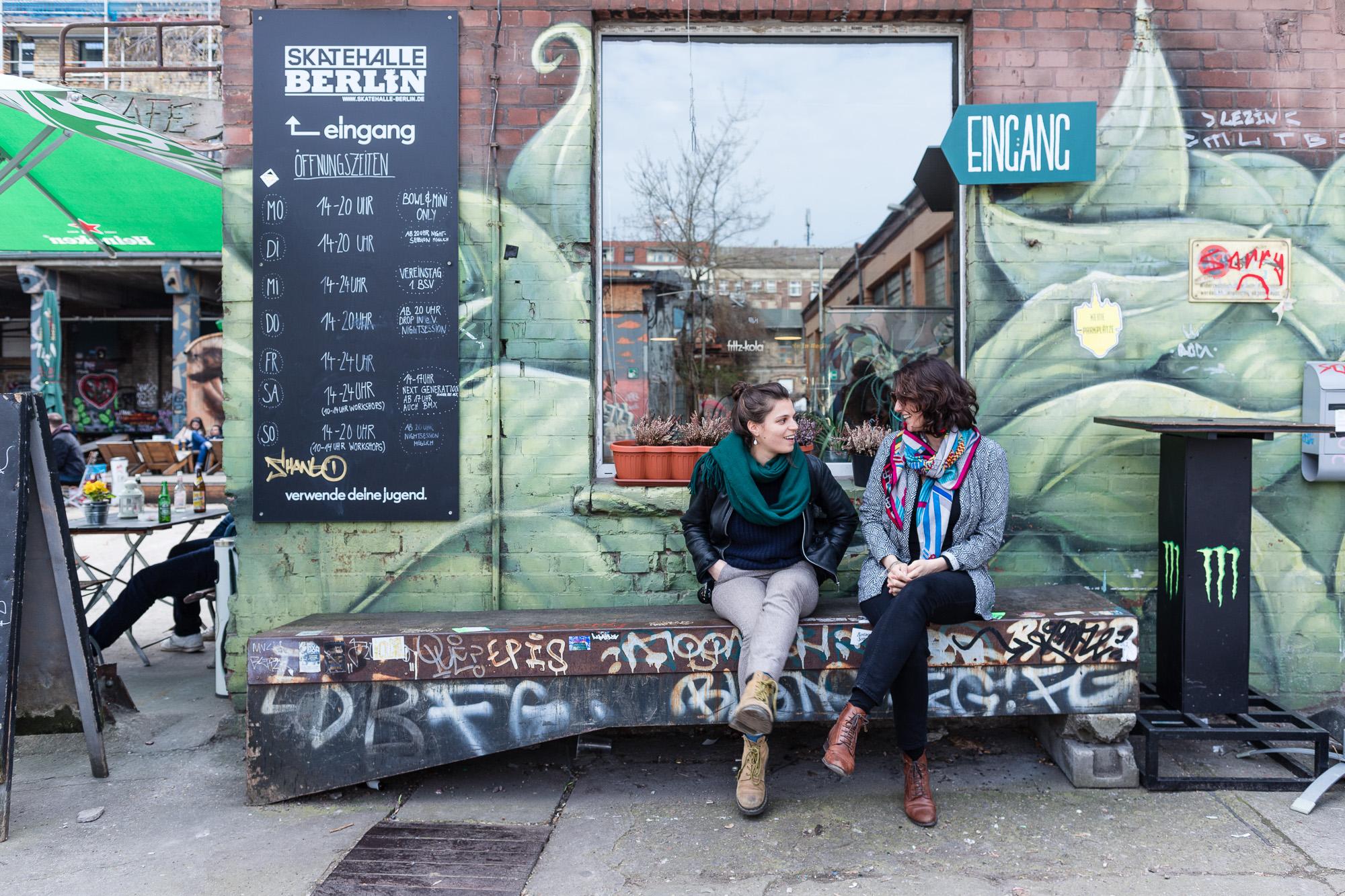 Femmes sur un banc devant une fresque à Berlin