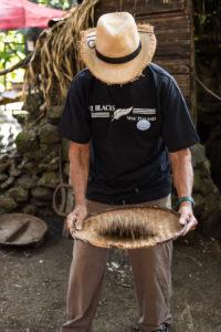 Homme au chapeau triant les baies de café